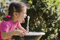 4818289-Young-girl-drinking-at-fountain-with-closed-eyes-tongue-sticking-out-and-water-frozen-mid-air-Stock-Photo