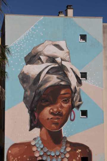 A mulher africana e o seus lenços. A pintura preferida das mulheres do bairro.